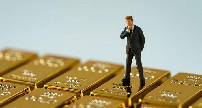 Hombre pensando sobre un montón de lingotes de oro